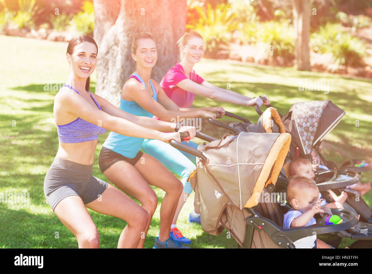 Women exercising with baby stroller in park - Stock Image
