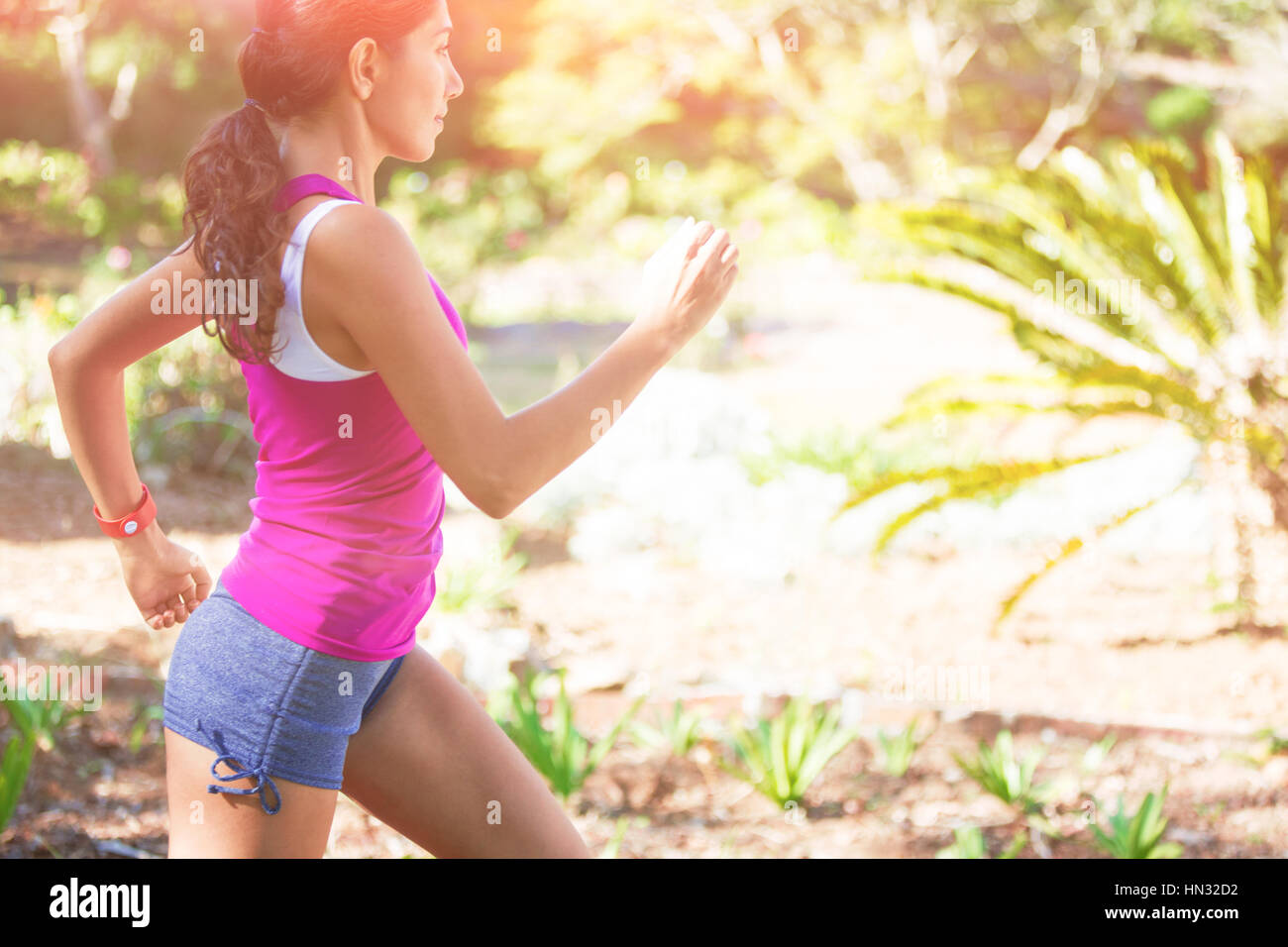 Woman exercising in park on sunny day - Stock Image