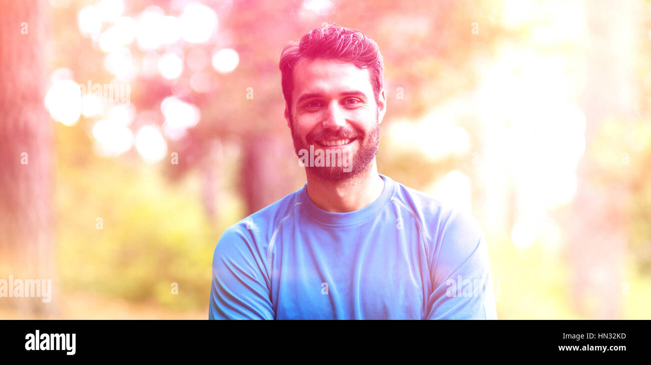 Portrait of smiling man standing in forest with arms crossed - Stock Image
