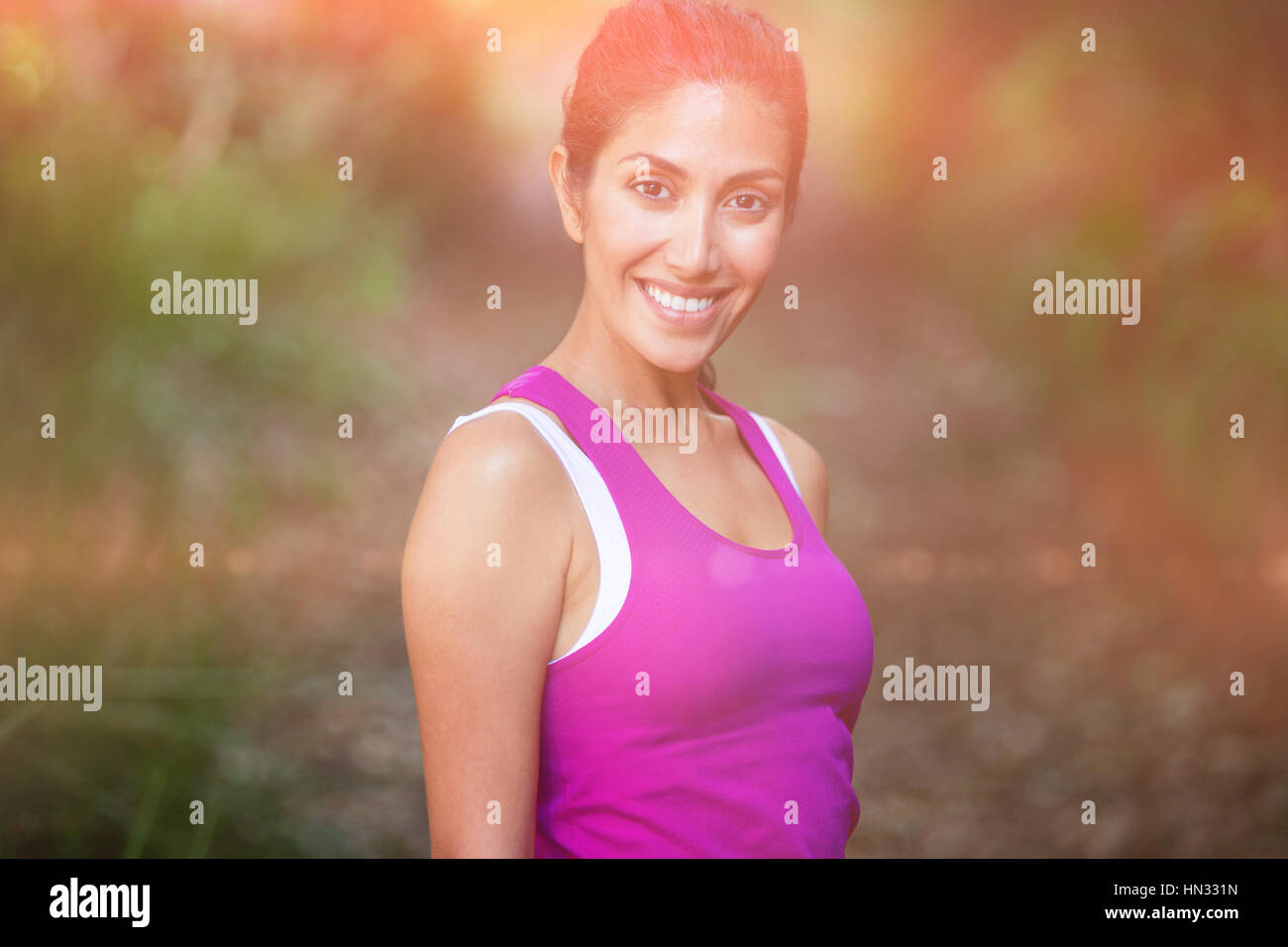 Portrait of smiling fit woman standing in park - Stock Image