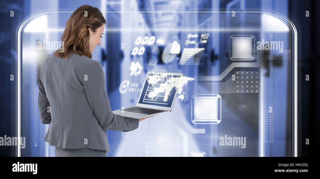 Rear view of businesswoman using laptop against image of data storage 3d Stock Photo