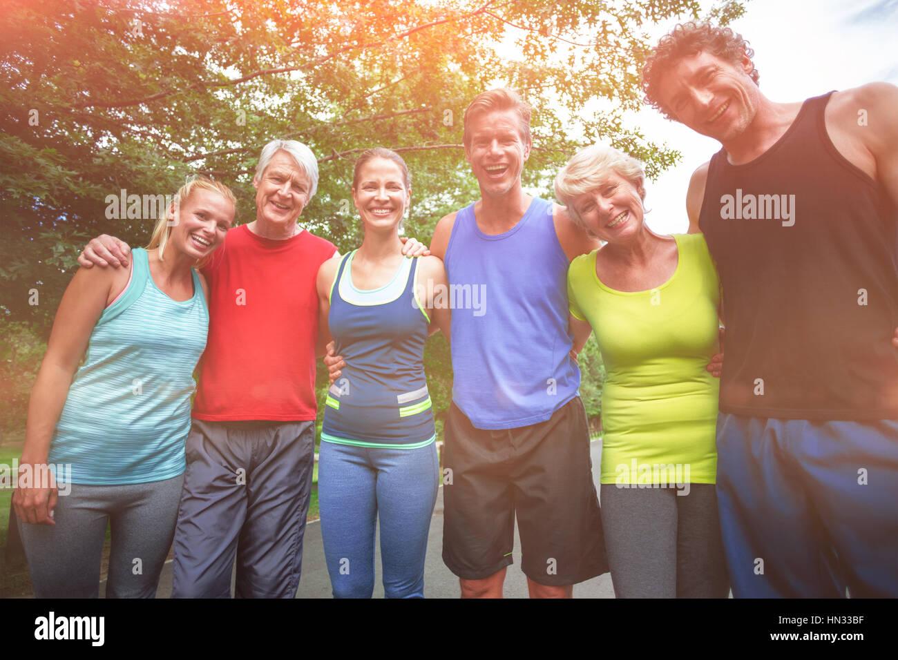 Portrait of marathon athletes posing in park - Stock Image