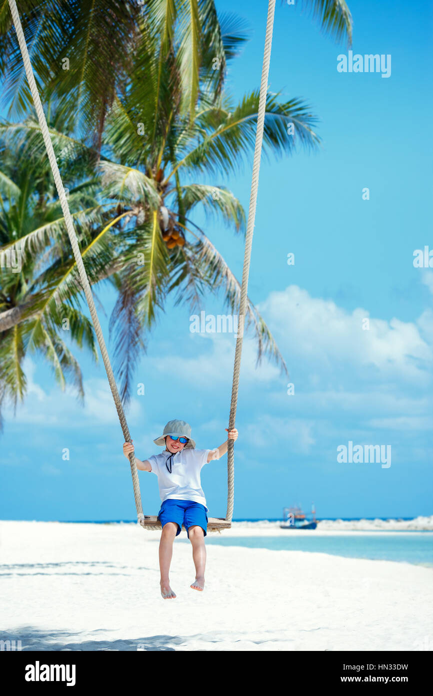 Cute boy having fun swinging at tropical island beach, Koh Phangan island. Thailand, Asia Stock Photo