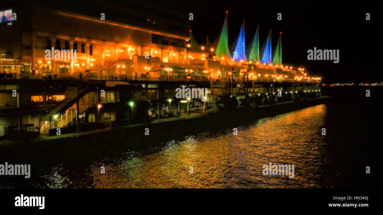 Illuminated buildings by river in city at night - Stock Image
