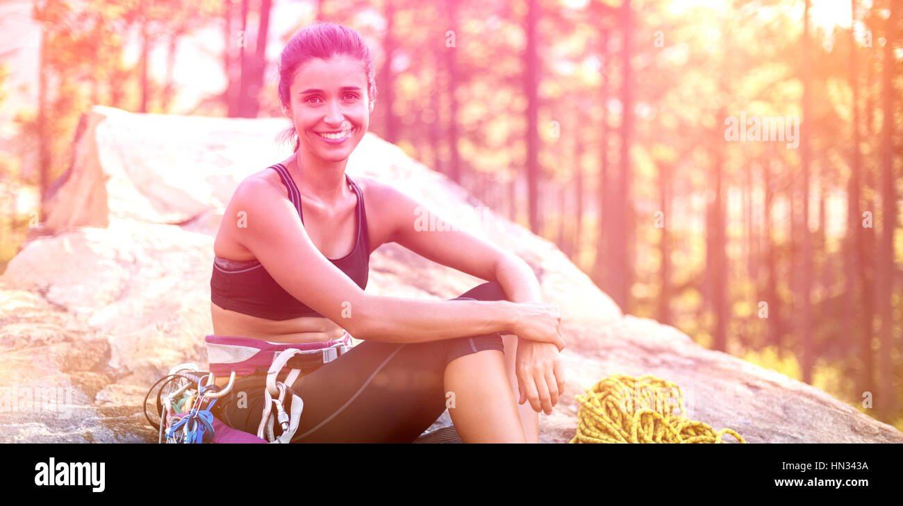 Woman smiling and sitting on a rock with climbing equipment - Stock Image