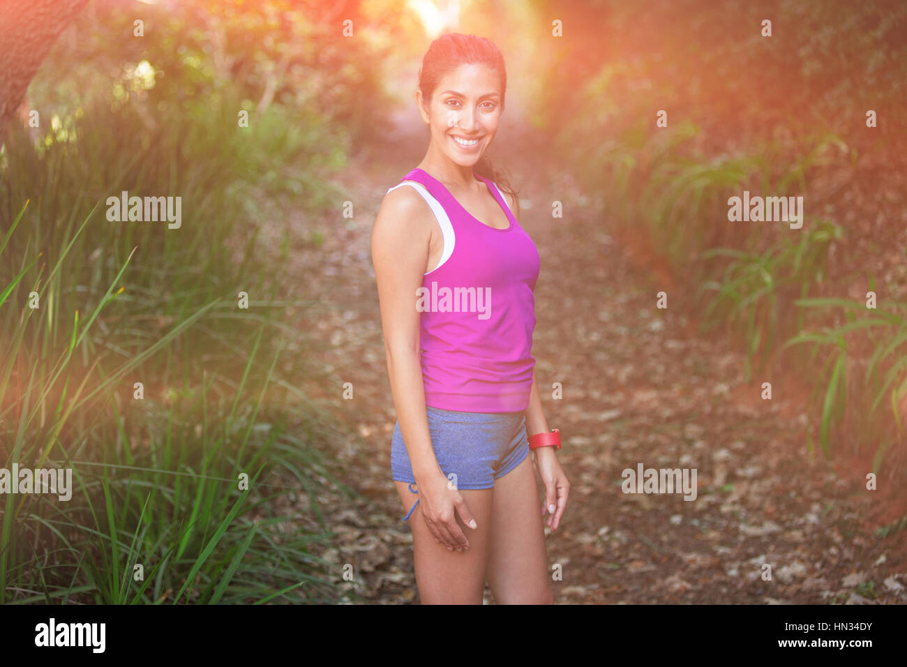 Smiling fit woman standing on field - Stock Image