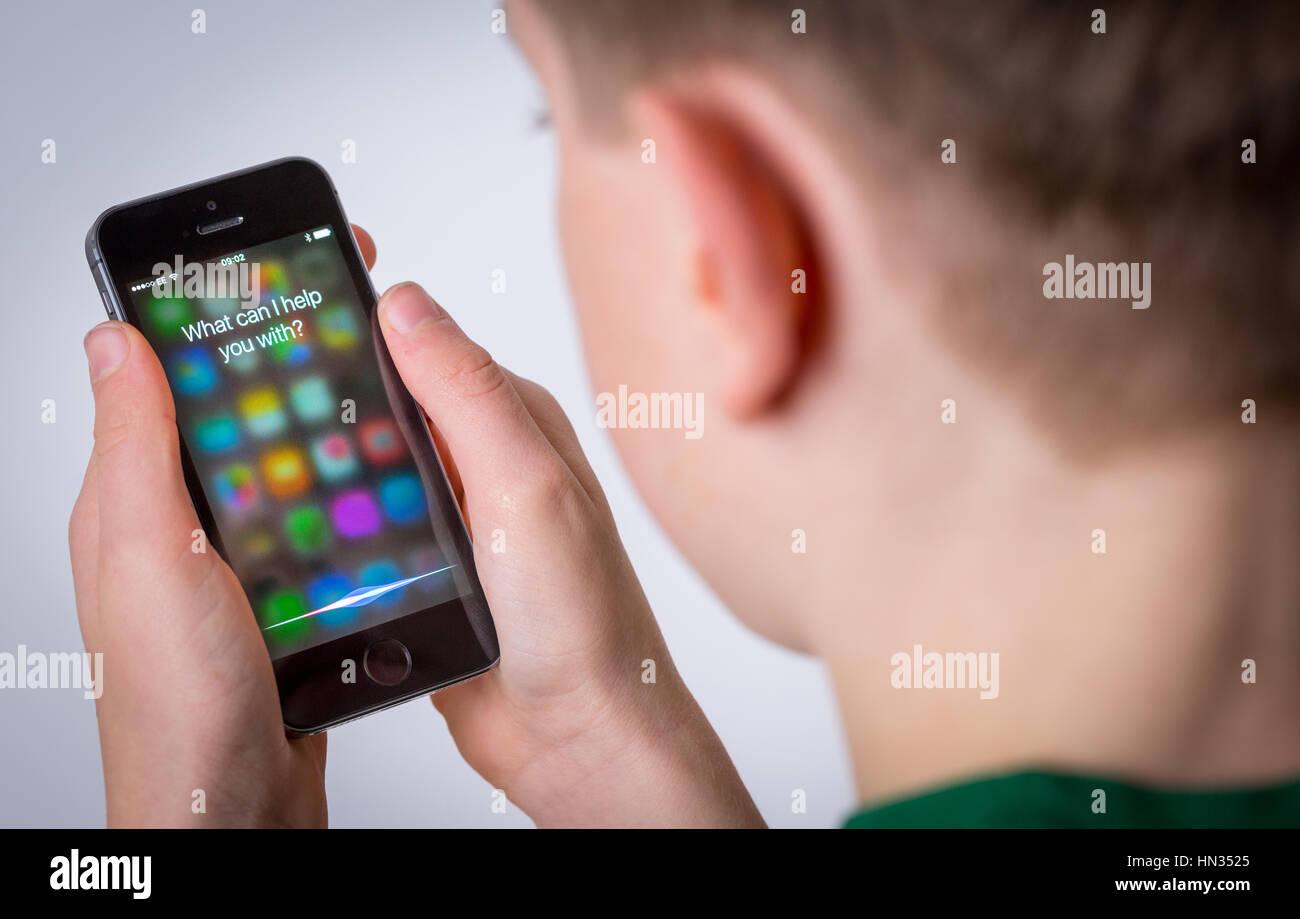 A teenage boy using Siri on an iPhone - Stock Image