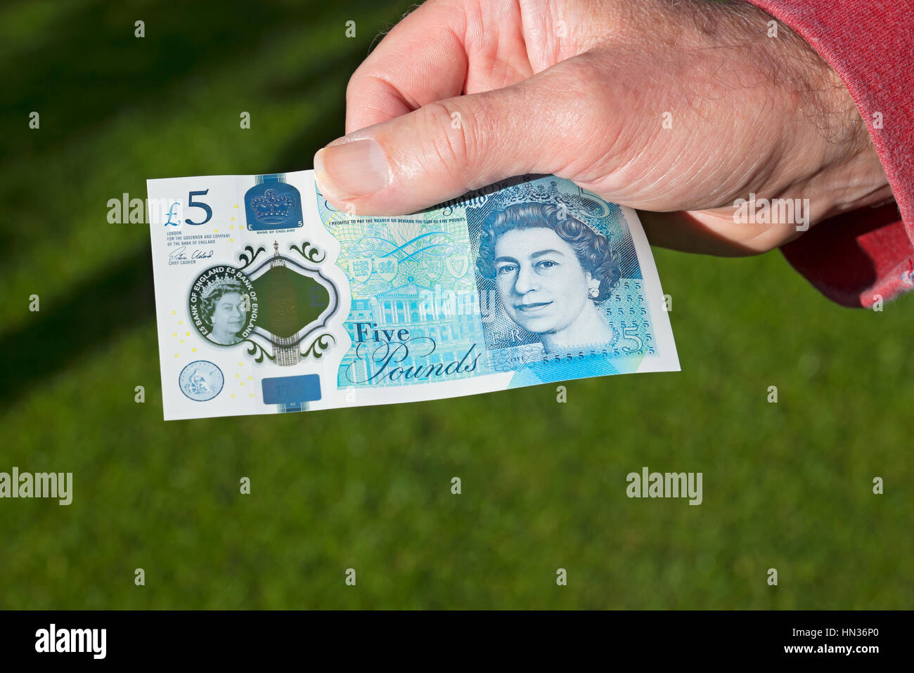 Man holding new polymer five pound note. - Stock Image