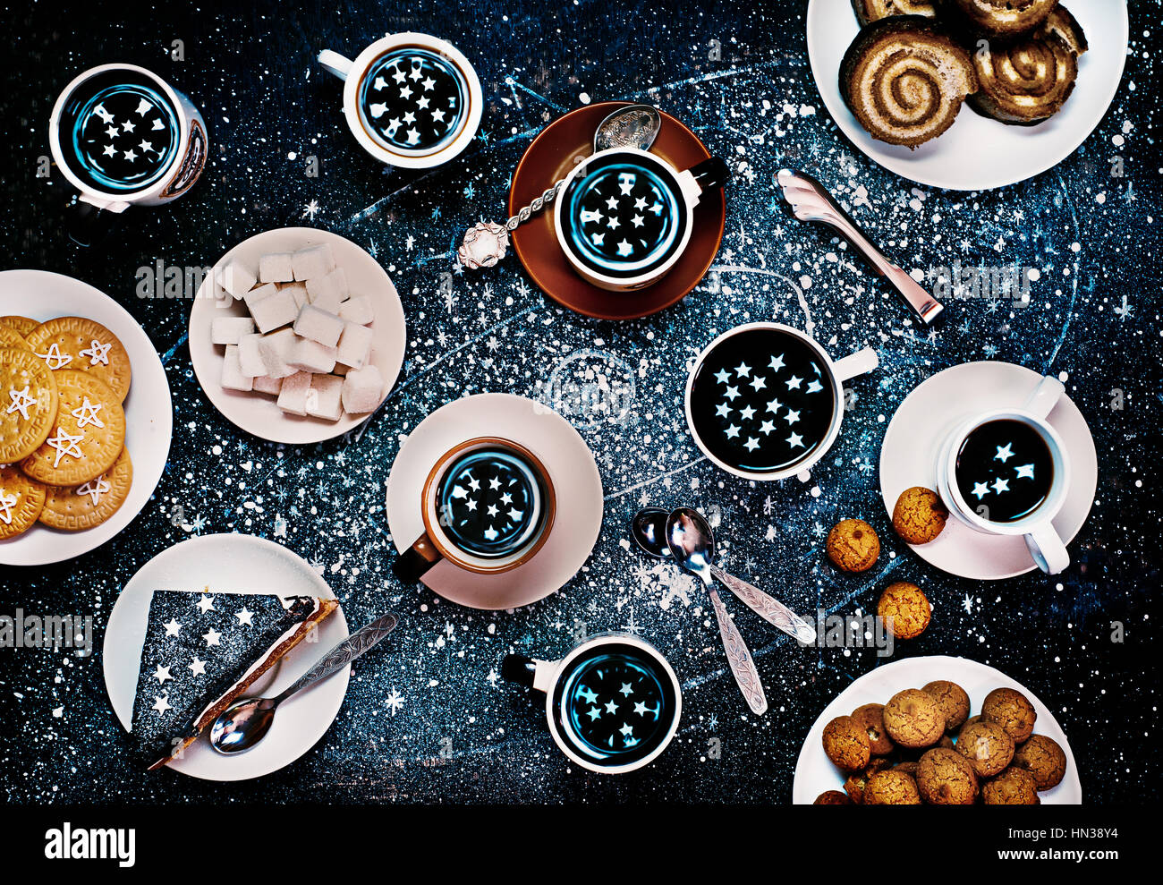 Tea party of astronomers, where the stars are reflecting in cups. Still life image shot from above. - Stock Image