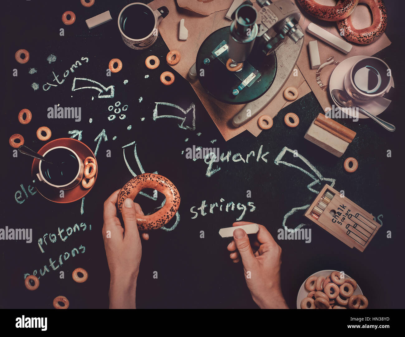 Still life with pastry, notes, microscope and research tools. A workplace of a scientist who gets inspired by ordinary - Stock Image