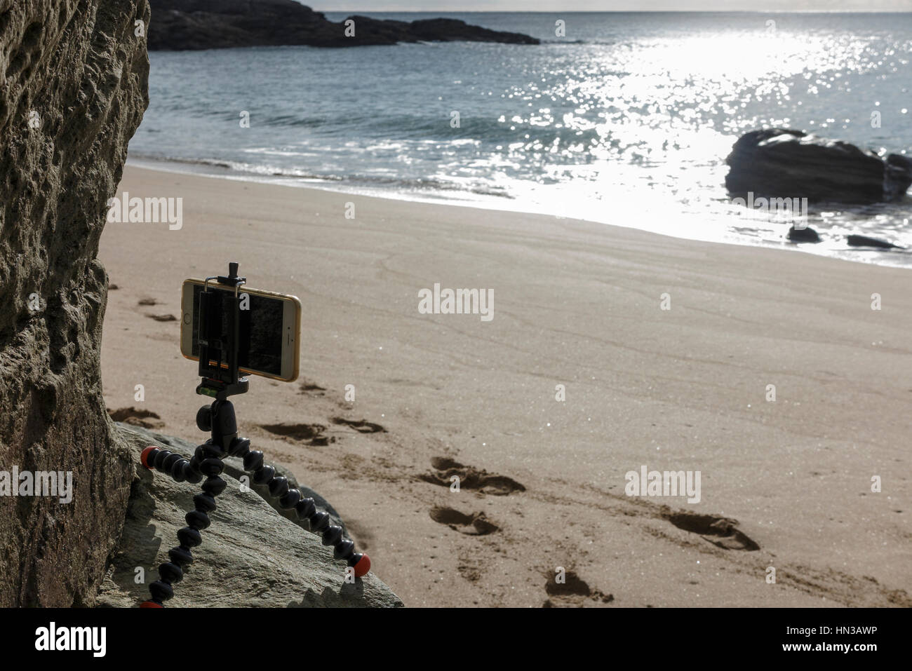 Using a small 'GorillaPod' tripod with an iphone to photograph beach in Devon - Stock Image