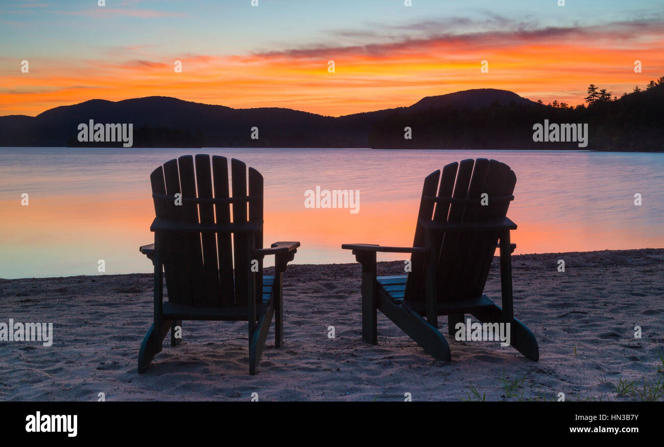 Silhouette Of Two Adirondack Chairs Near Blue Mountain Lake Shoreline    Stock Image