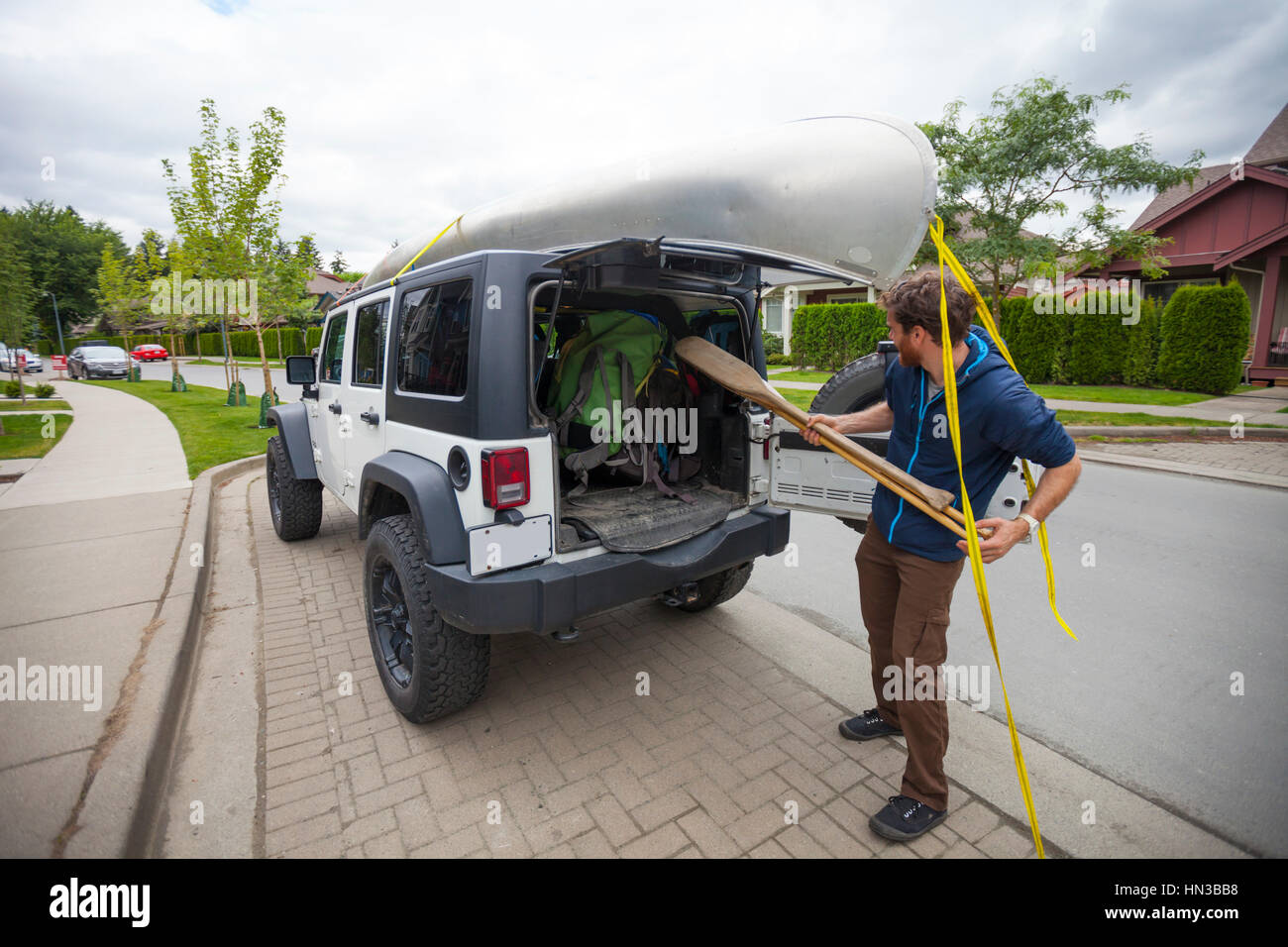 An Adventurer Loads Canoe Paddles Into The Back Of His Jeep - Stock Image