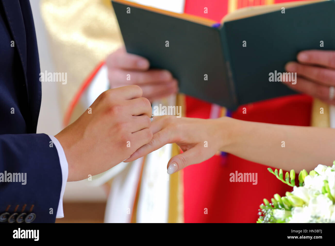 Bride and groom during wedding rings exchange at the church - Stock Image