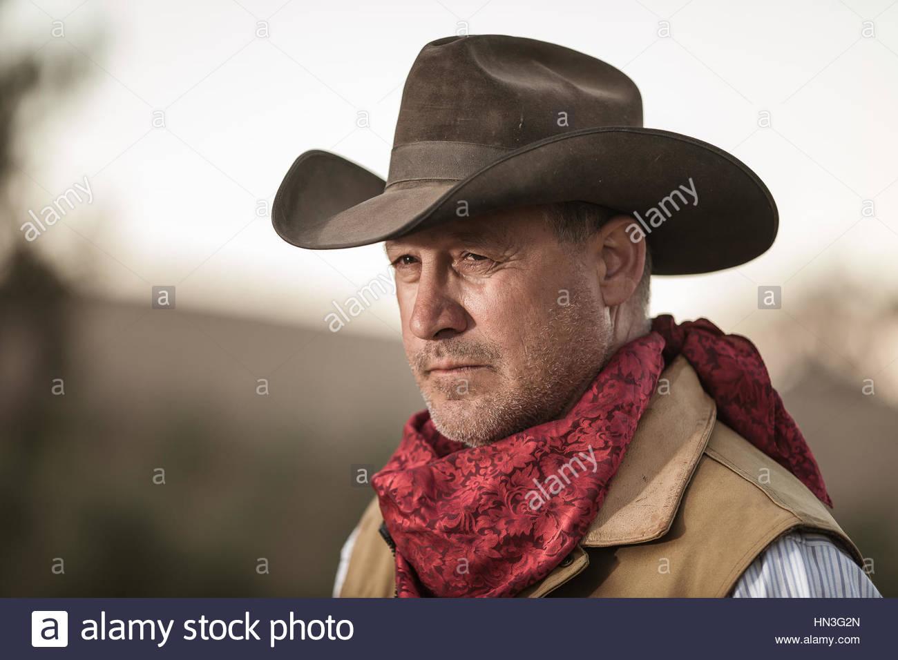 portrait of a cowboy in profile wearing a cowboy hat vest