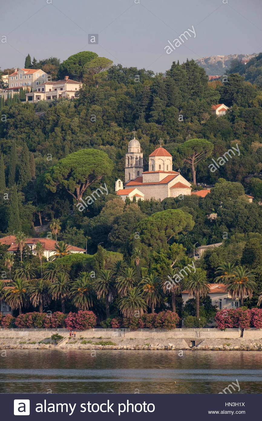 Early morning sunlight shines on a church on a green hillside in Zelenika, Montenegro. - Stock Image