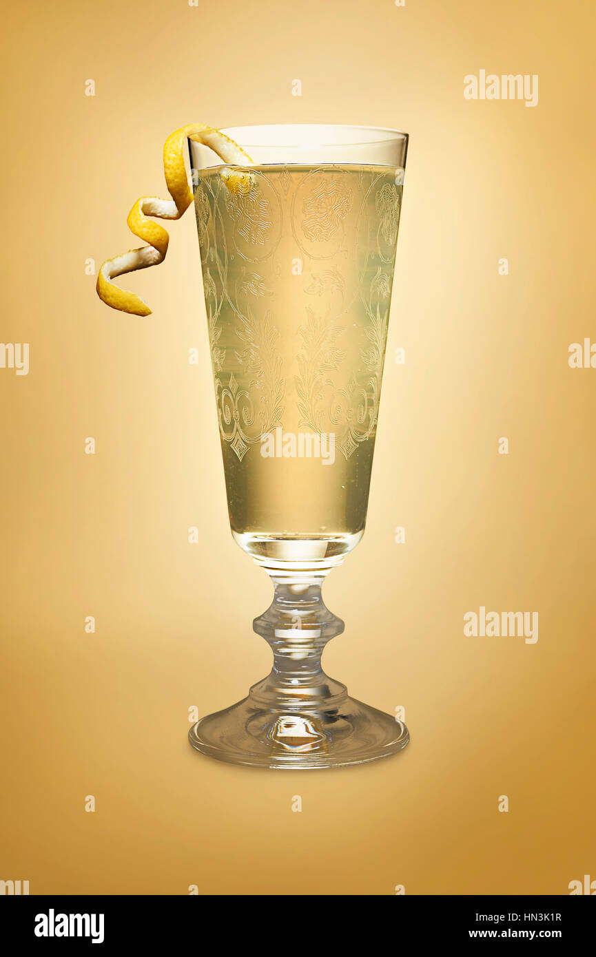 Single gold cocktail in glass with a lemon twist on yellow gold background - Stock Image