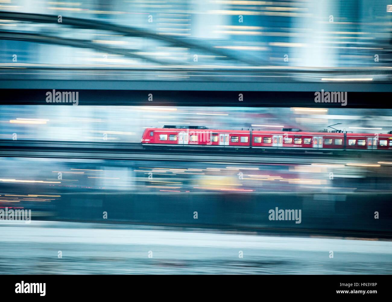 ARCHIV - Ein Regionalzug rollt am 31.01.2017 in Frankfurt am Main (Hessen) früh morgens auf einer Eisenbahnbrücke - Stock Image