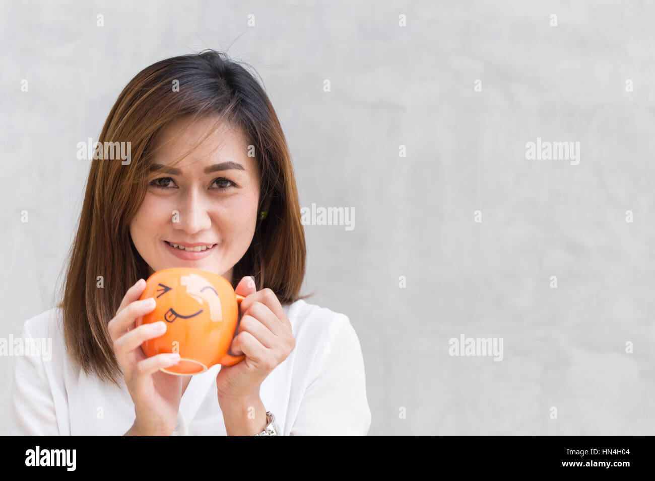 happy drink coffee concept with copy space, Asian girl teen working women adult handle smile mug. - Stock Image