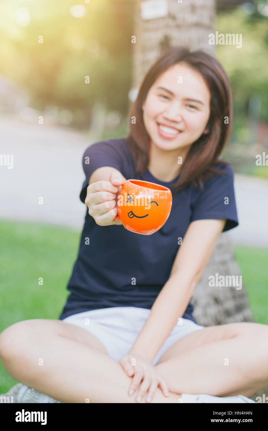 happy drink coffee concept with copy space, Asian girl teen working women adult handle smile mug in the green park. - Stock Image
