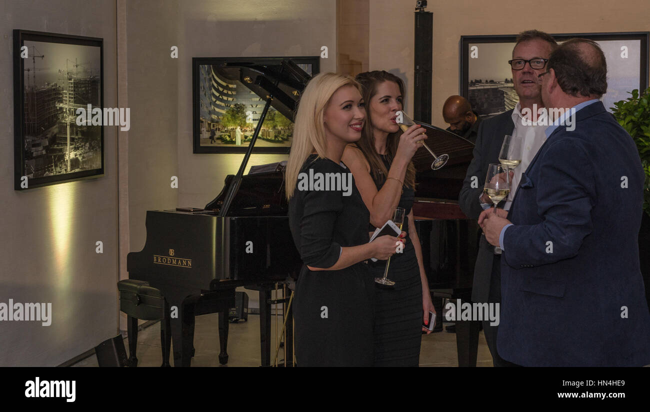 Businessmen and Women gathered at a company event with drinks and in smart business attire. - Stock Image