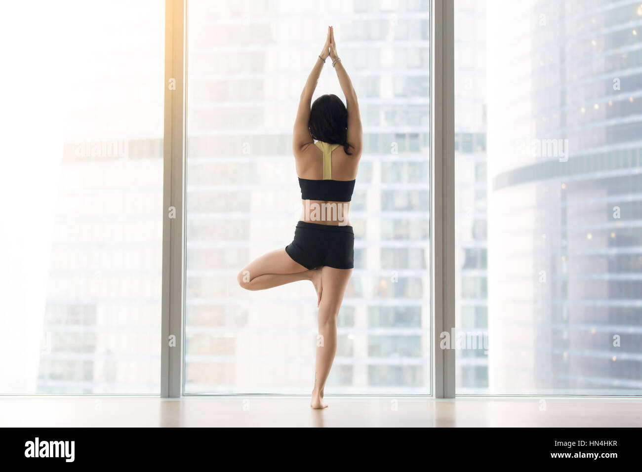 Young woman in Vrksasana pose against floor window, rear view Stock Photo