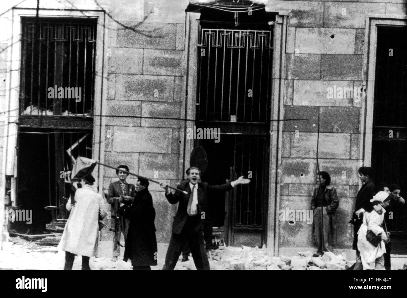 November 1956, Budapest, rebels assault the building behind the tank. The attack is a success, and a standard bearer Stock Photo