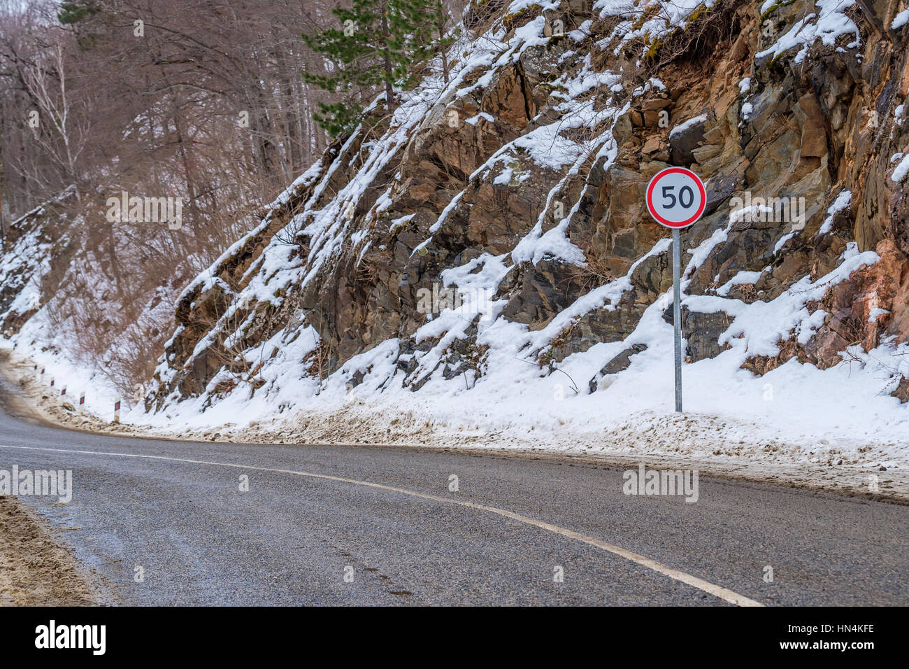 Round road sign limiting speed up to 50 km per hour on mountain road in winter warning about danger curve on slippery - Stock Image