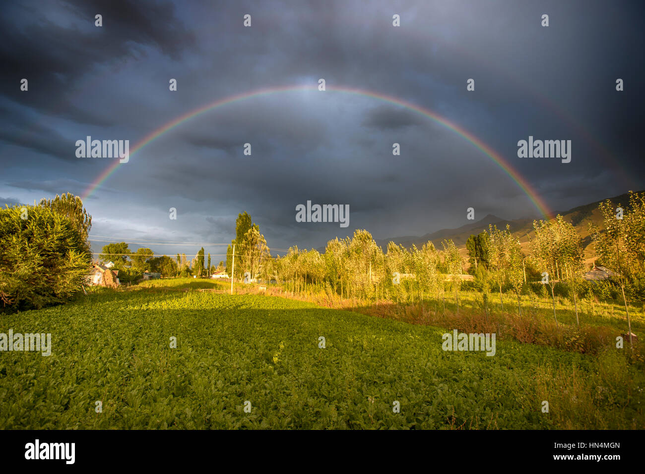 Rainbows over farm land or Chon Kemin, Kyrgyzstan - Stock Image