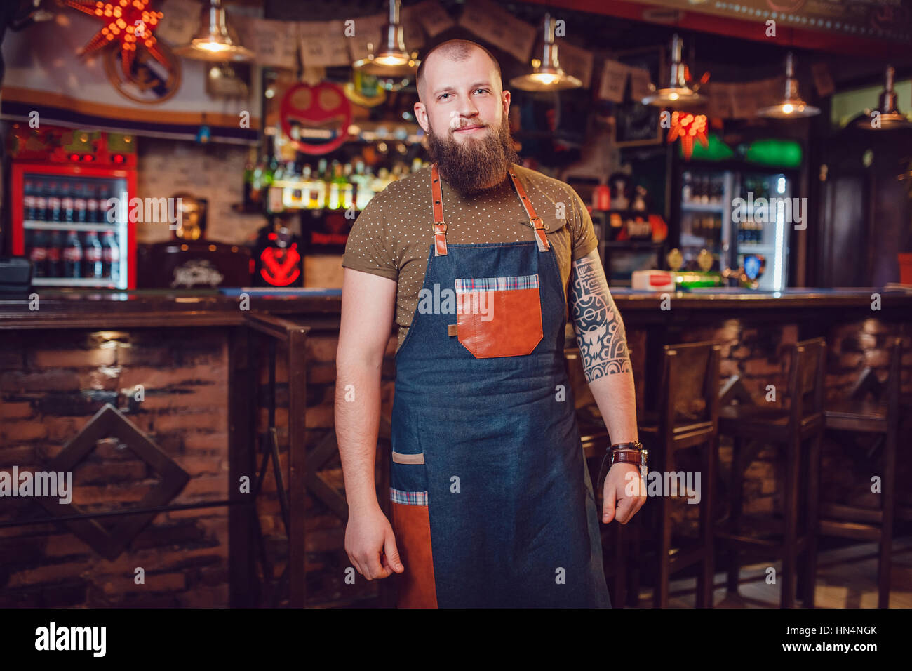 Bearded barman with tattoos and watches wearing an apron standing near the bar. Stock Photo