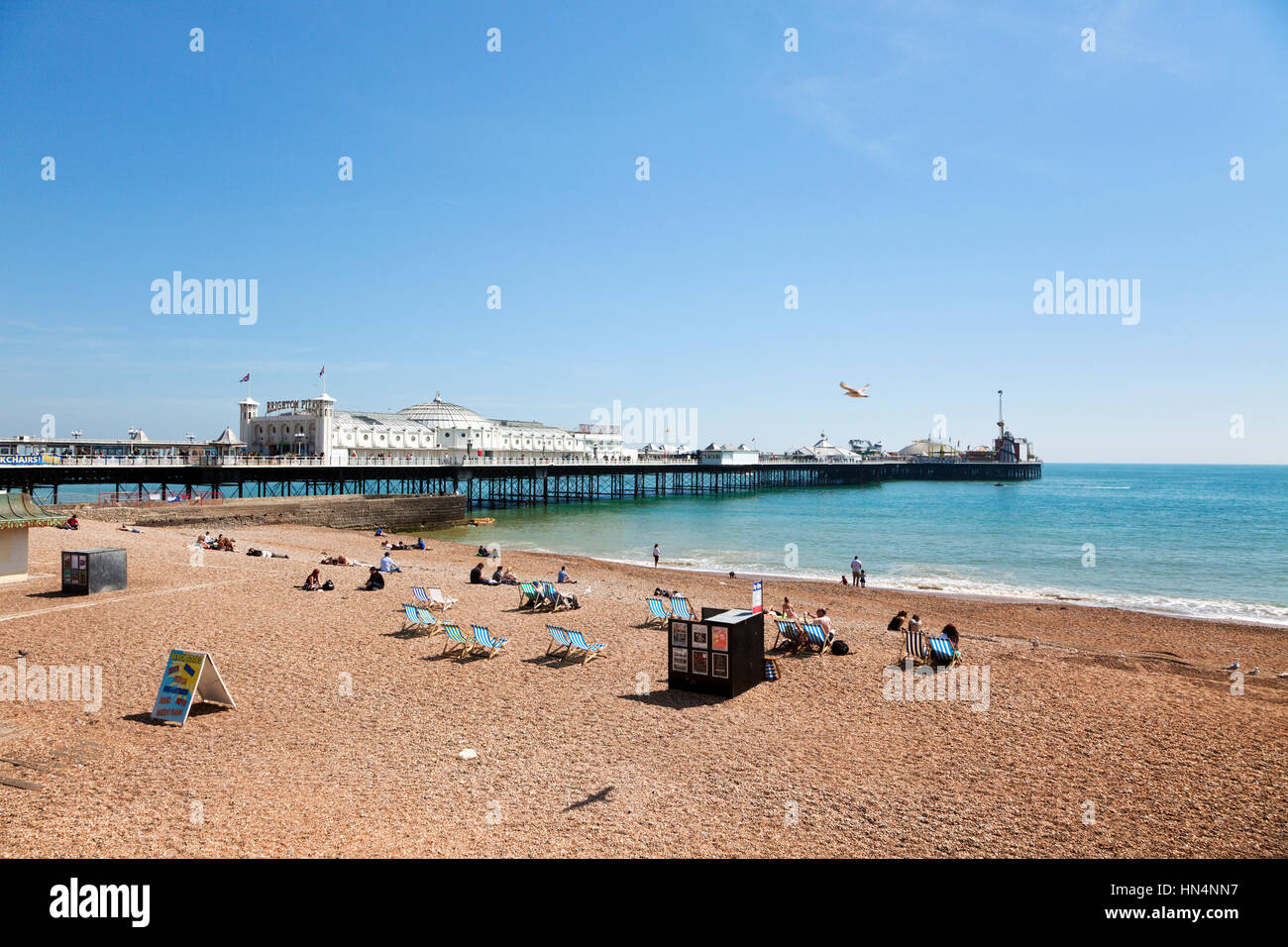 Brighton, Sussex, United Kingdom - May 16, 2014: Tourists relaxing on the beach next to the Brighton Pier from 1899. - Stock Image