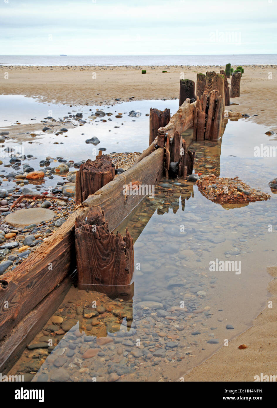 An old eroded wooden breakwater on the beach at Mundesley, Norfolk, England, United Kingdom. - Stock Image