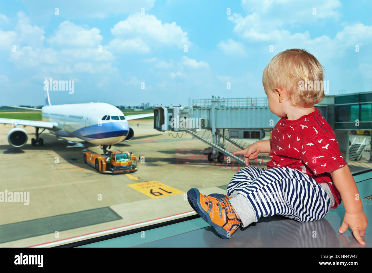 Little baby boy waiting boarding to flight in airport transit hall and looking through the window at airplane near - Stock Image