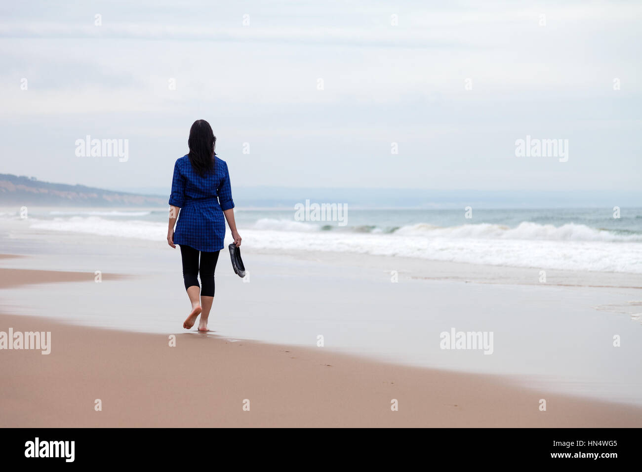 Young woman walking away alone in a deserted beach on an Autumn day / woman beach walking alone lonely sad sadness - Stock Image