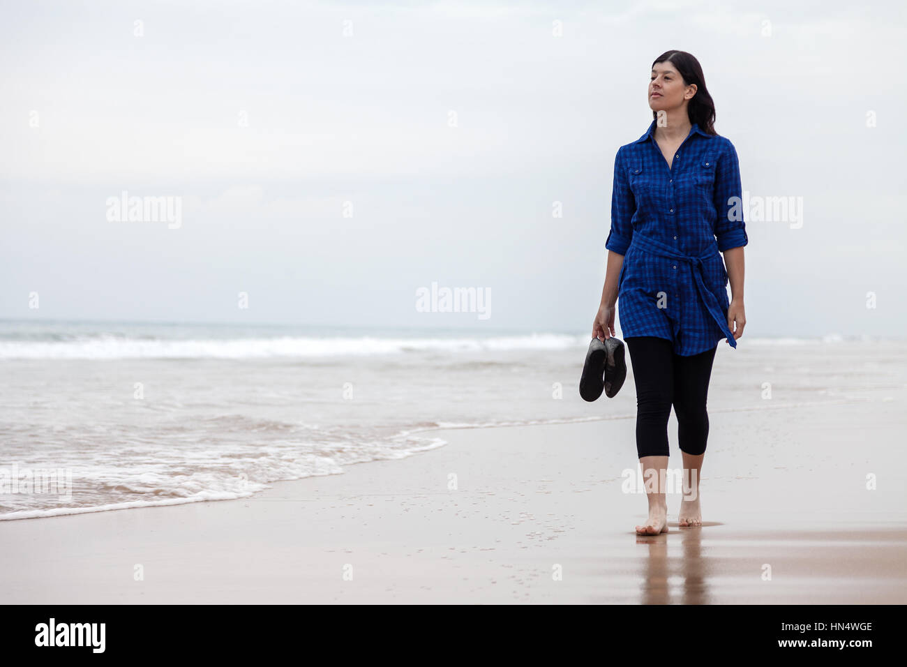 Young woman walking alone in a deserted beach on an Autumn day /  woman beach walking alone lonely sad sadness depression - Stock Image