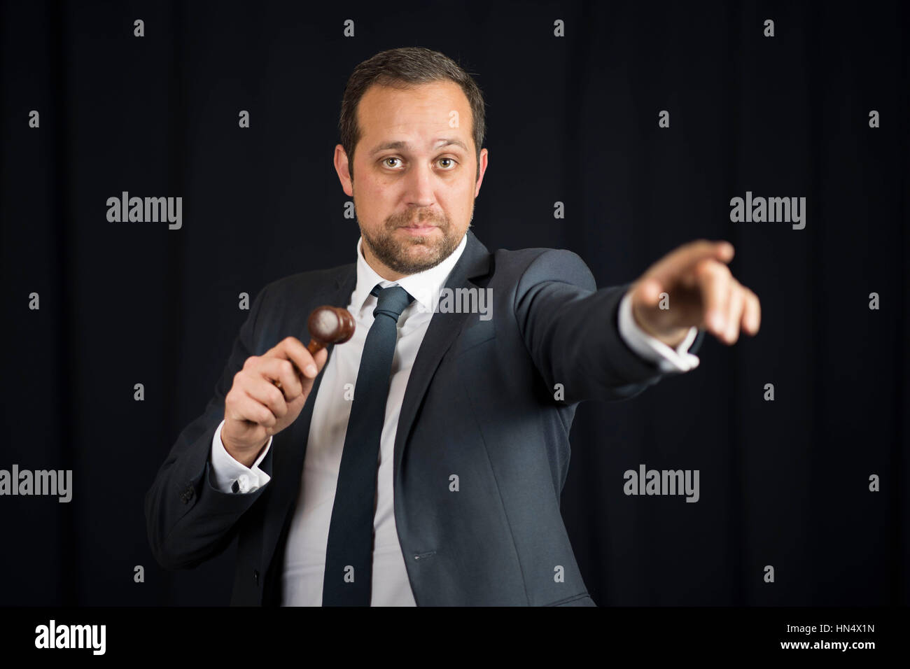 A male auctioneer in action holing a gavel during a live auction. Stock Photo