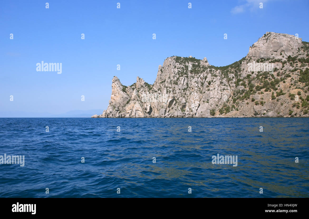Nice humpbacked mountain in the sea against blue sky - Stock Image