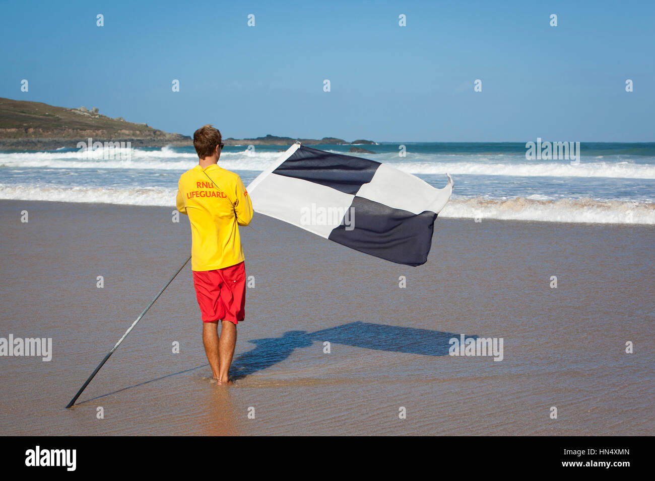 St Ives, United Kingdom - September 11, 2011: A lifeguard from the Royal National Lifeboat Institution (RNLI) stands - Stock Image