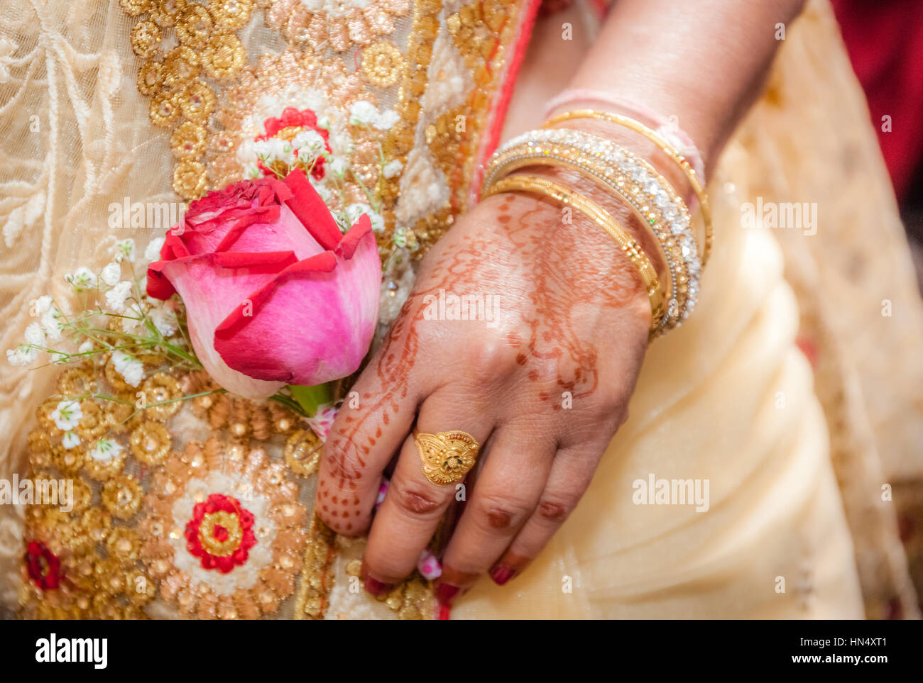 Indian Bride Hand Painted With Henna Tattoo Holding A Red Rose