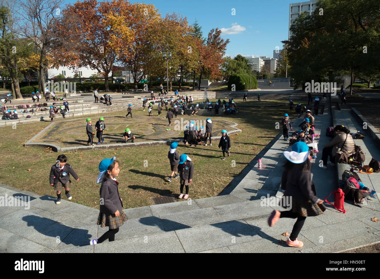 Young Japanese students, school children playing, having fun in Central Park (Chuo Koen) in Hiroshima, Japan, Asia - Stock Image