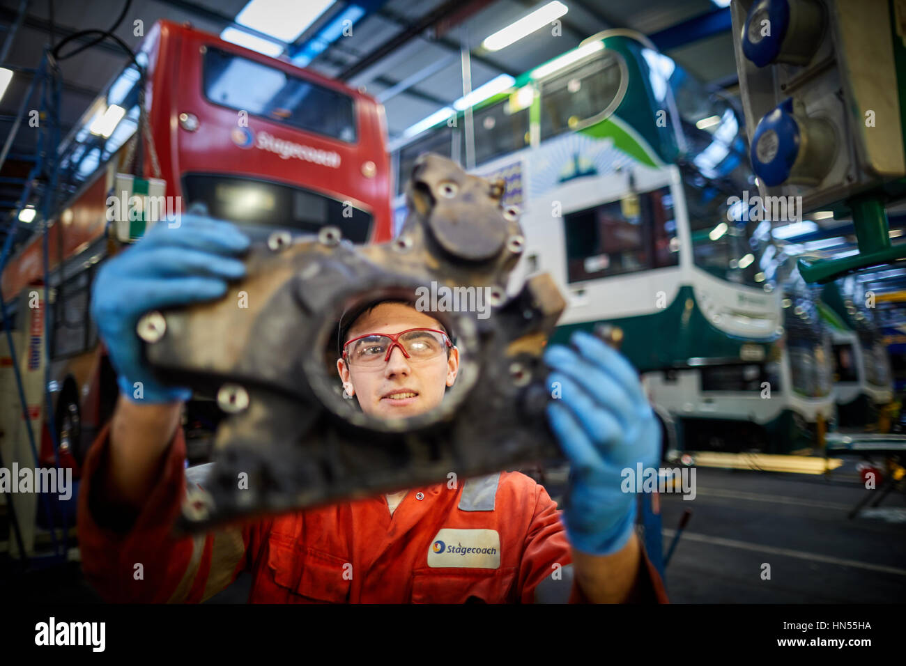 A young teenage apprentice fitter mechanic fixing broken down double decker bus engine at Stagecoach bus operators - Stock Image