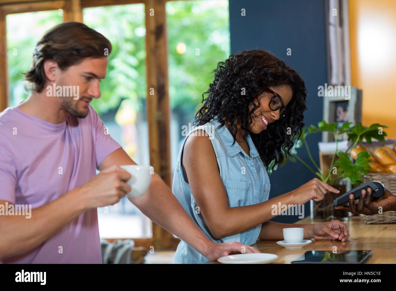 Woman entering pin code on credit card reader at counter in café - Stock Image