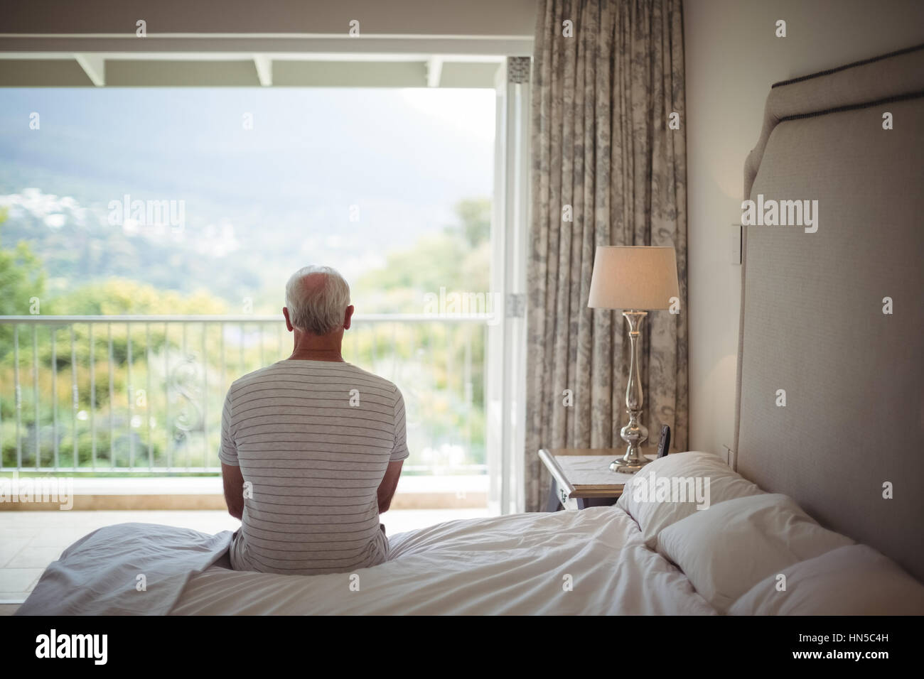 Senior man in bedroom looking at the view through the window - Stock Image