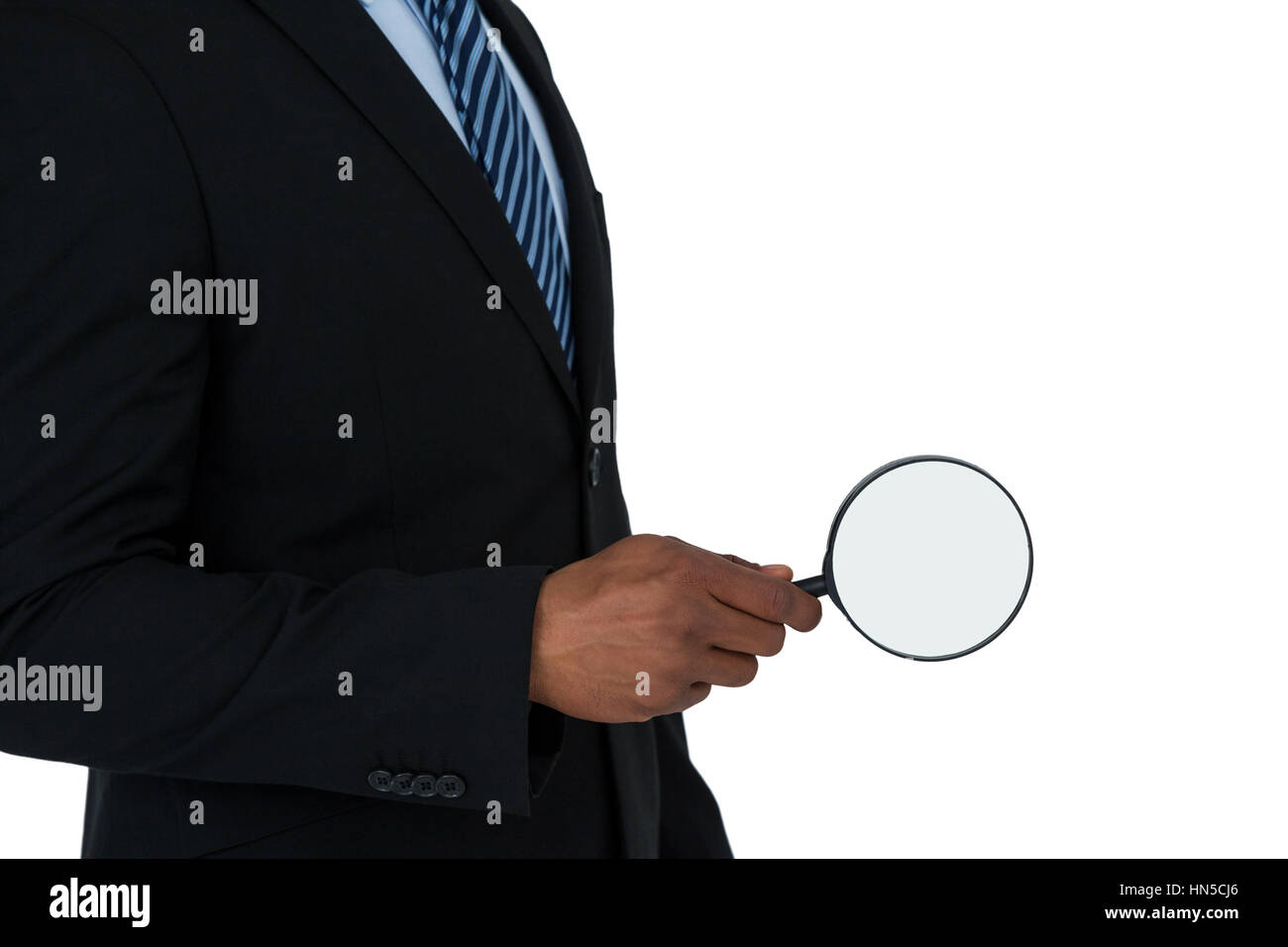 Mid section of businessman holding magnifying glass on white background Stock Photo