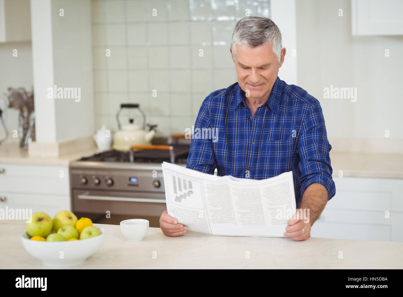 Senor man reading newspaper in kitchen at home - Stock Image