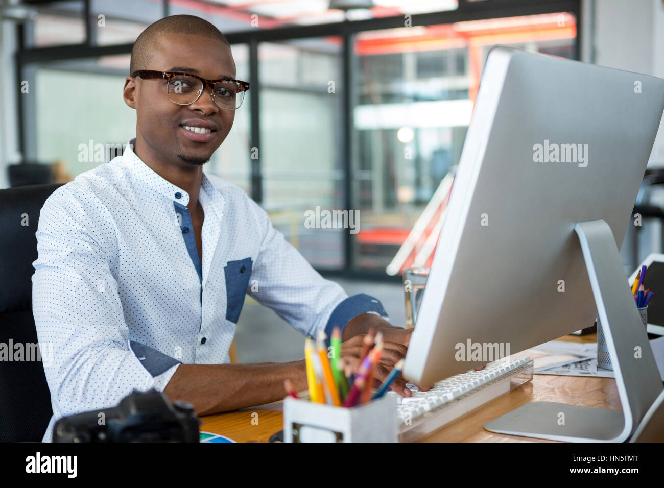 Portrait of graphic designer working at desk in office - Stock Image