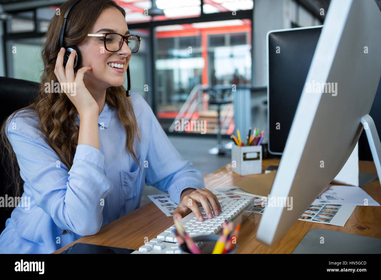 Female graphic designer working over computer at desk in office - Stock Image