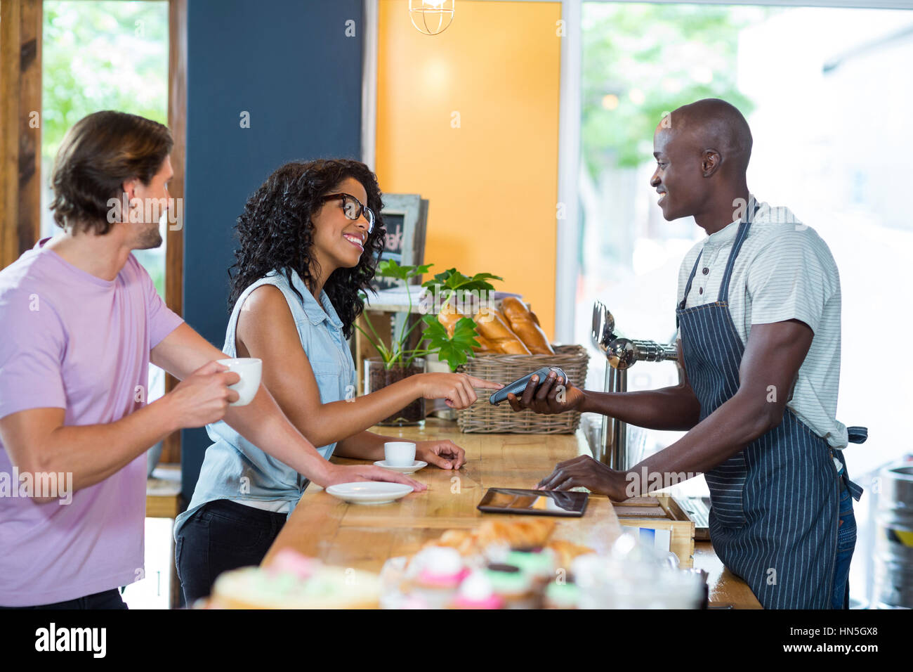 Woman entering pin code on credit card reader at counter in café Stock Photo