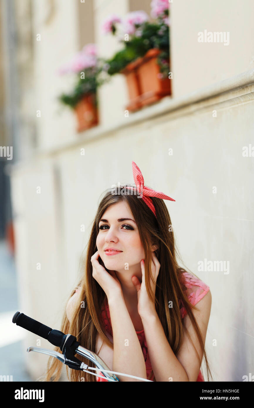 sensitive girl, looking at camera, sitting on a bicycle - Stock Image