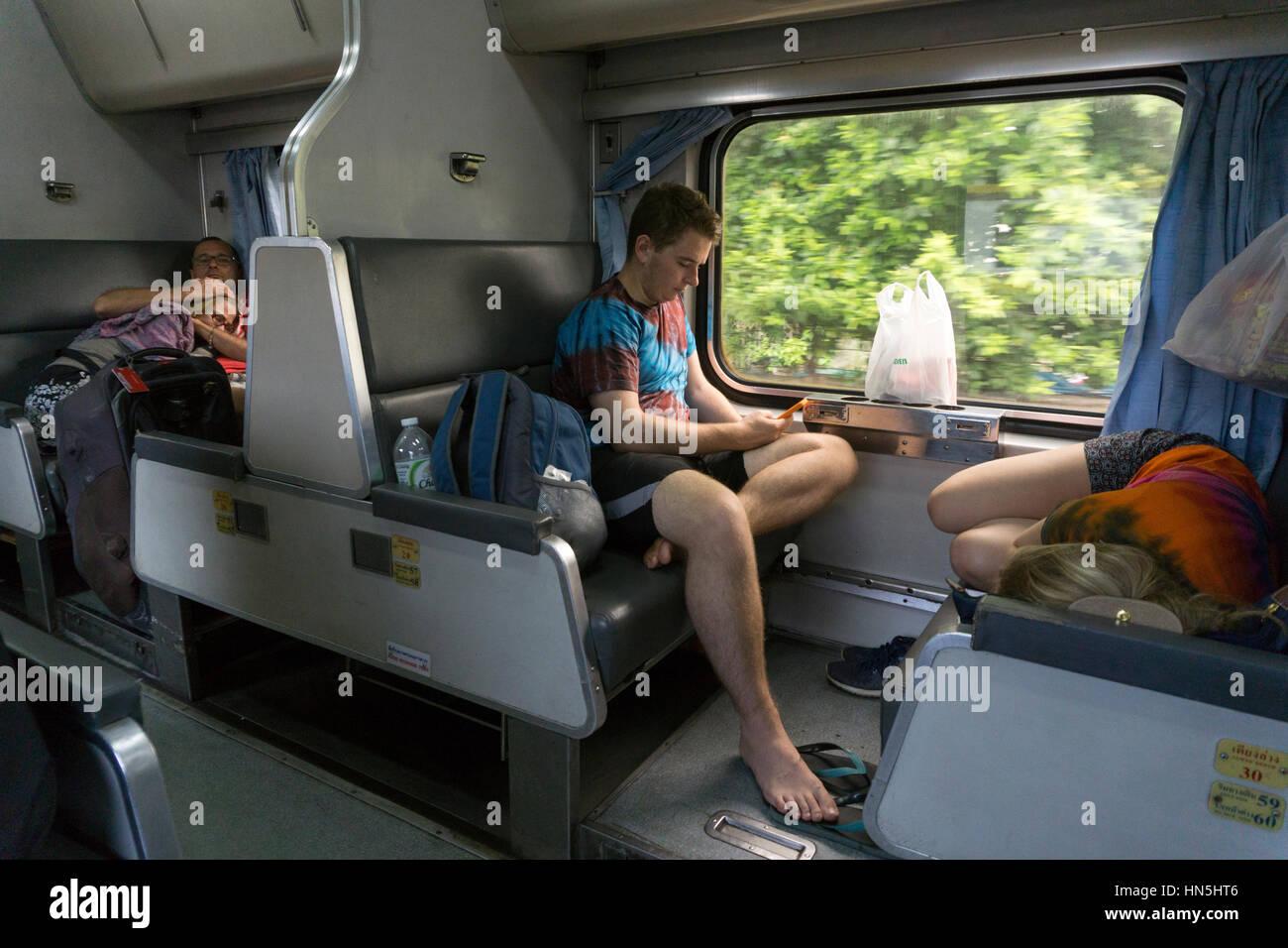 Travellers on the sleeper train between Chiang Mai and Bangkok - Stock Image